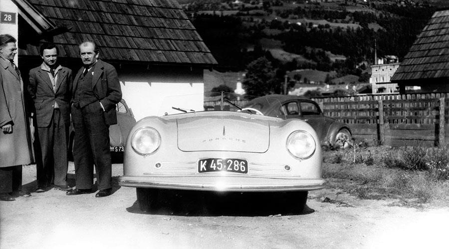 最初のポルシェである356ナンバーワンロードスターは1948年、オーストリアのグミュントという山間の小さな街の外れの小屋から生み出された。中央がそのナンバーワンロードスター、後方の人物は、向かって右がフェルディナント・ポルシェ博士、中央がその長男フェリー・ポルシェ、左がボディ設計主任兼チーフデザイナーのエルヴィン・コメンダ。