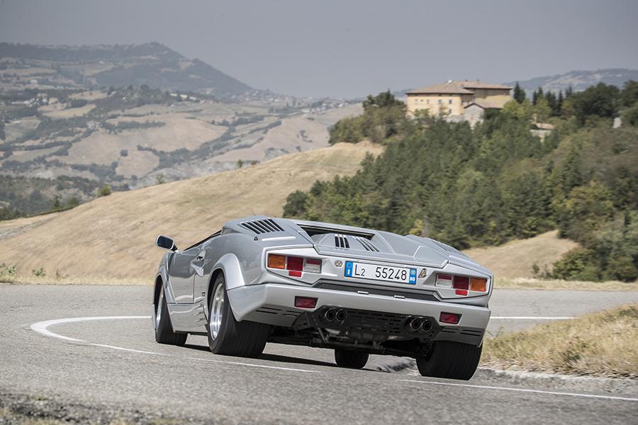 イタリアのカントリーサイドのワインディングロードを走るクアットロヴァルヴォーレのリアビュー、5.2リッター4バルブV12の爆音が聞こえてきそうだ!