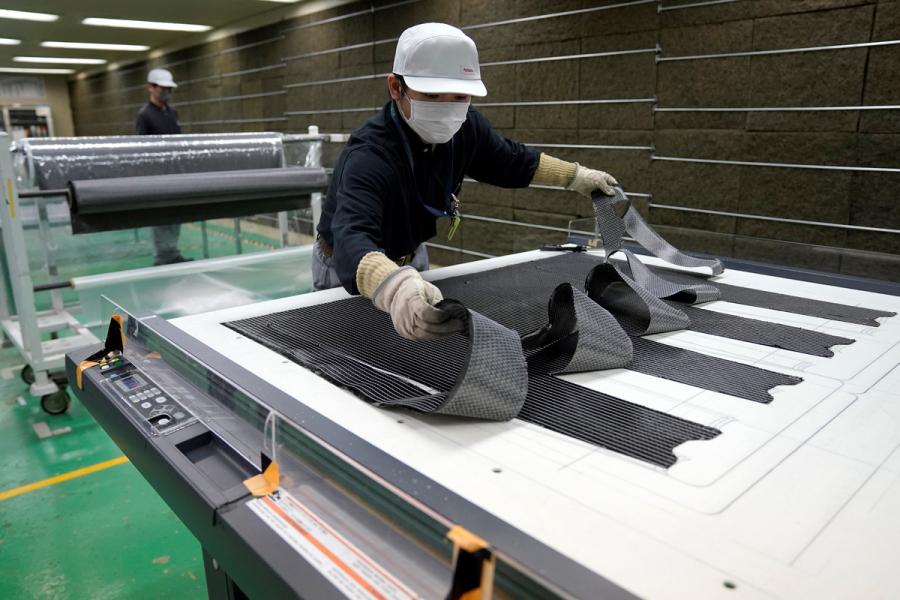 炭素繊維シートをカッティングし、シートを必要な枚数だけ重ね合わせつつ織物を成形していくところ。