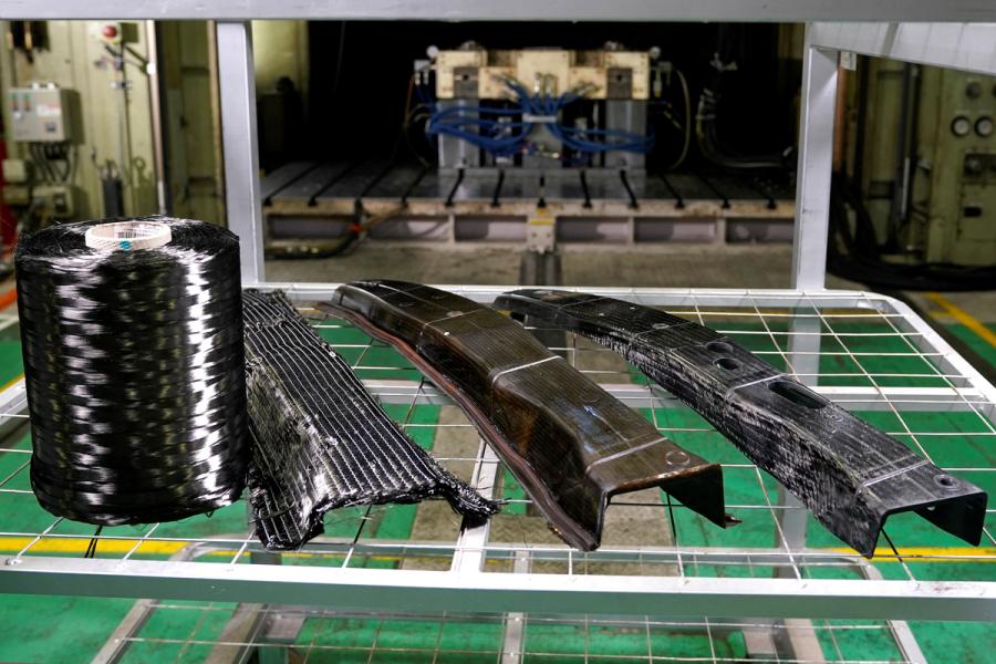 左から炭素繊維のロール、炭素繊維シートから作ったパーツ、金型、成形機で完成させたCFRP製パーツ。