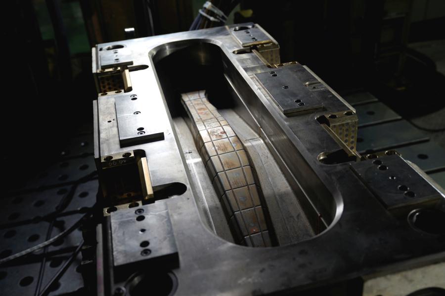 成形機にセットされたCFRP製パーツ用の金型(オス型)。