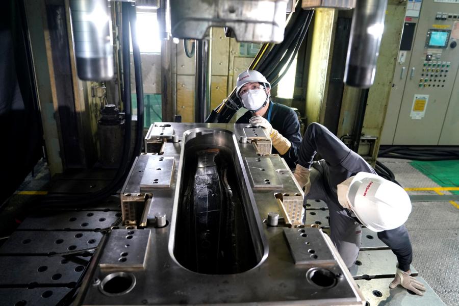 成形機にセットされた金型(オス型)の上にCFRPシートから作ったパーツがセットされたところ。