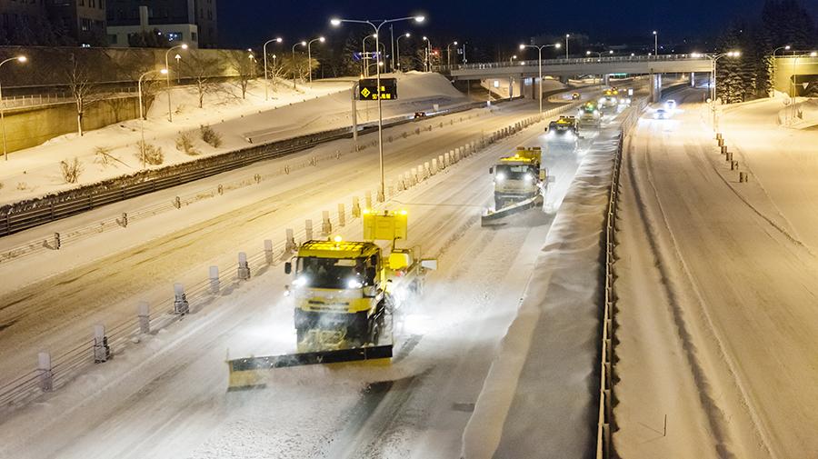 プラウを操作しながら運転する除雪トラック