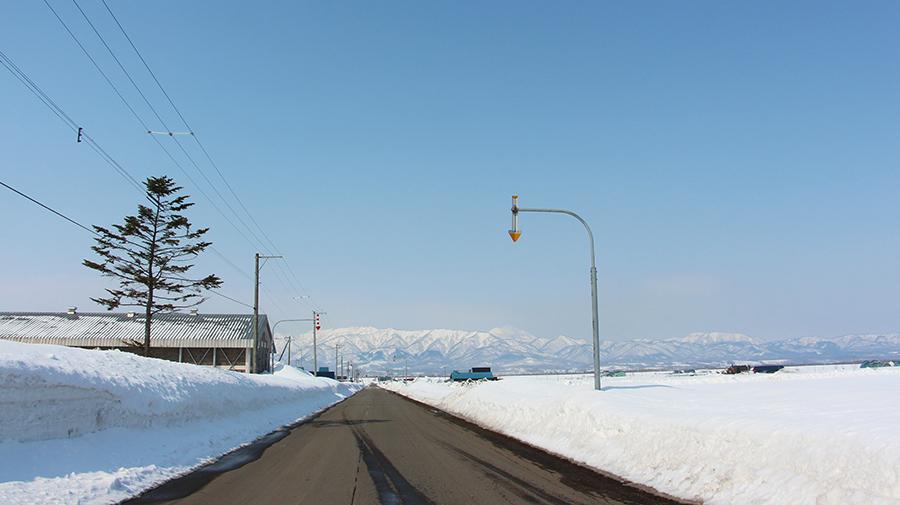 高い雪堤が隣接する道路
