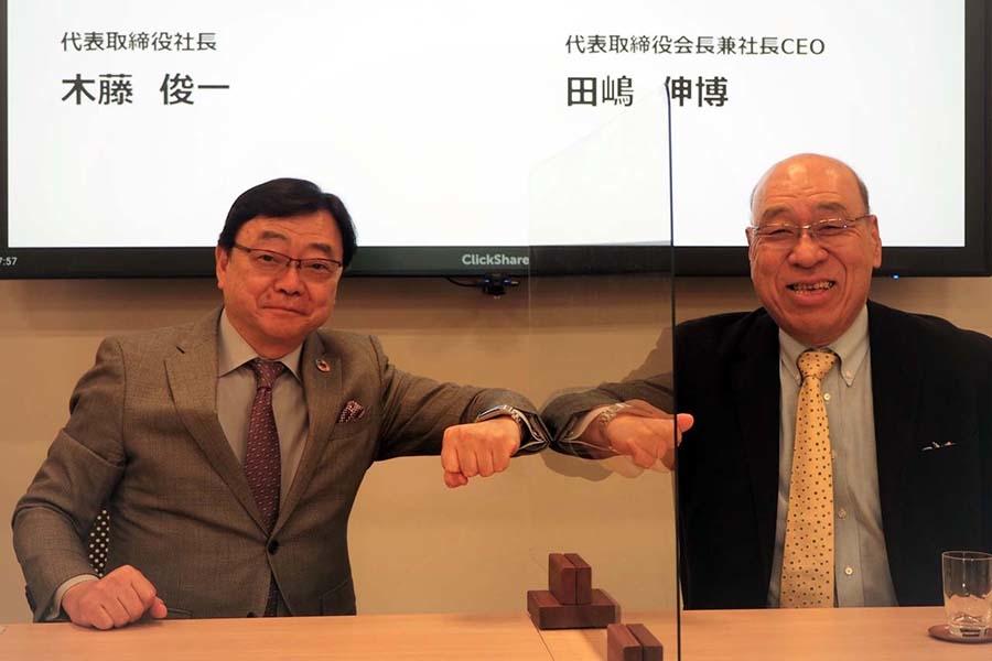 記者会見を終え、アクリル板越しに肘タッチする出光興産の代表取締役社長の木藤俊一氏(左)と、タジマモーターの代表取締役会長兼社長CEOの田嶋伸博氏