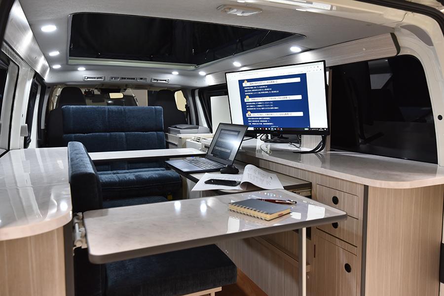 車内にはオフィス用のデスクやシート、冷蔵庫も完備。セカンドシートレイアウトは前向き、後ろ向き、フラットと状況に合わせて3つの展開が可能で、車中泊のベッドとしても利用できる。