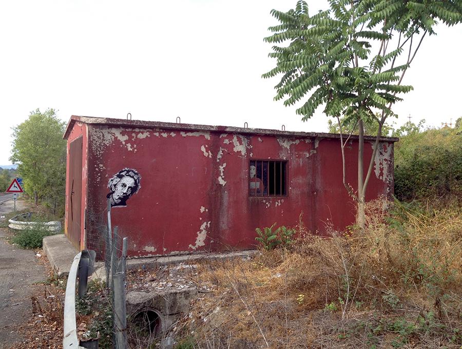 筆者が住むシエナにあるANASの資材小屋。外壁の落書き以上に、窓から覗いている人形が不気味だ。